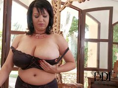 Big breasted chubby brunette Kora displays her massive naturals after