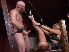 Blonde Mistress Nicholette enjoys dominating this bald guy in her dungeon