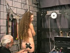 Slut with long curly hair takes electrified clamps on her ass and tits